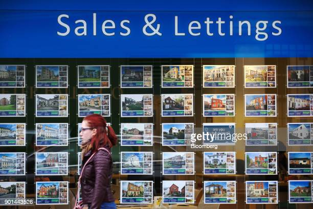 A pedestrian passes a display of properties for sale or rent at an estate agent's window in Cheltenham UK on Thursday Jan 4 2018 Cheltenhamin...