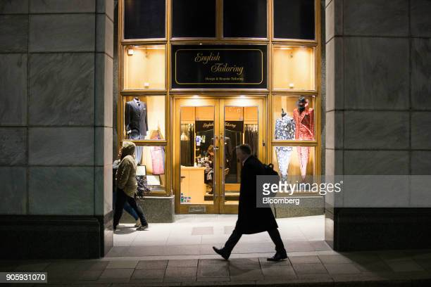 A pedestrian passes a English Tailoring shop at the Canary Wharf financial shopping and business district in London UK on Tuesday Jan 16 2018...