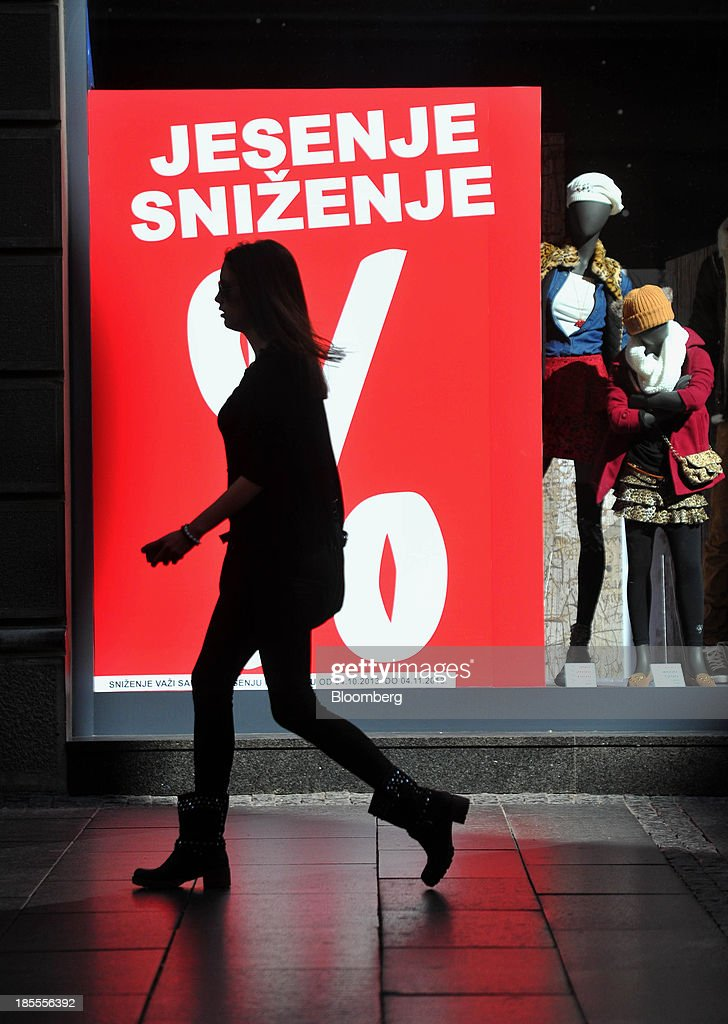 A pedestrian passes a fashion clothing store displaying a discount sign in Belgrade, Serbia, on Monday, Oct. 21, 2013. Serbia's government revealed a salvo of measures to bring the public finance deficit and debt back under control by 2017 after the head of the largest coalition party warned the country was on the brink of insolvency. Photographer: Oliver Bunic/Bloomberg via Getty Images