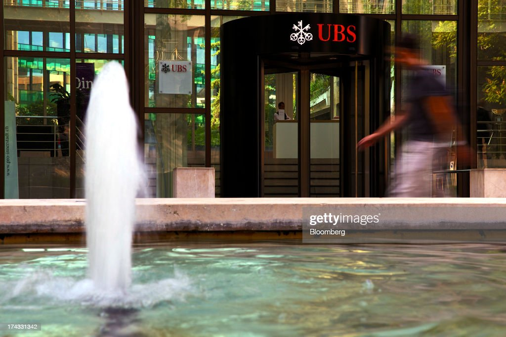 A pedestrian passes a fountain outside the offices of UBS AG in Basel, Switzerland, on Tuesday, July 23, 2013. Europe's biggest banks, which more than doubled their highest-quality capital to $1 trillion since 2007 to meet tougher rules, may have further to go as regulators scrutinize how lenders judge the riskiness of their assets. Photographer: Gianluca Colla/Bloomberg via Getty Images