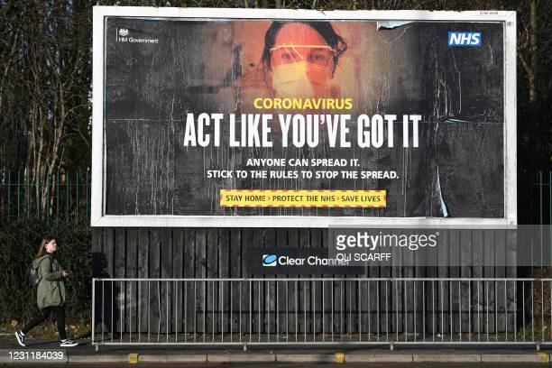 Pedestrian passes a Government Covid-19 information poster near a road in Manchester, northern England, on February 15, 2021. - Britain intends to...
