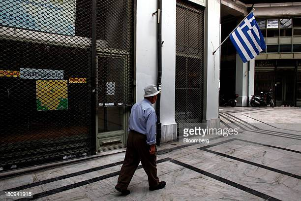 A pedestrian passes a Greek national flag hanging outside a closed store in an empty shopping mall during a 48hour strike by Greece's biggest...