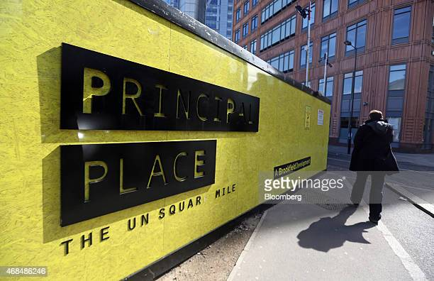 Pedestrian passes a hoarding surrounding the construction site of Principal Place, a joint development by Brookfield Property Partners LP, Concord...