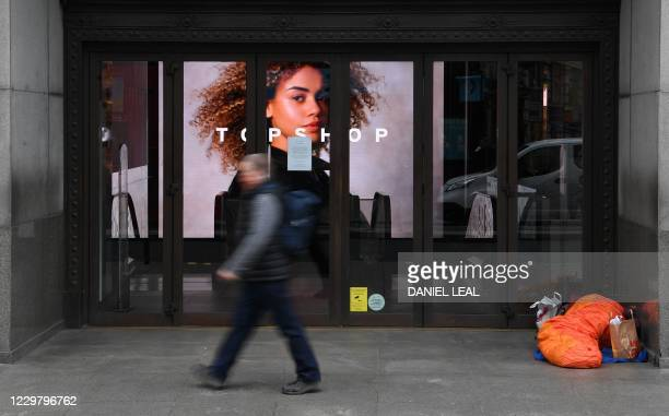 Pedestrian passes a homeless person sheltering in the doorway of a temporarily closed-down shop on an almost deserted Oxford Street in London on...