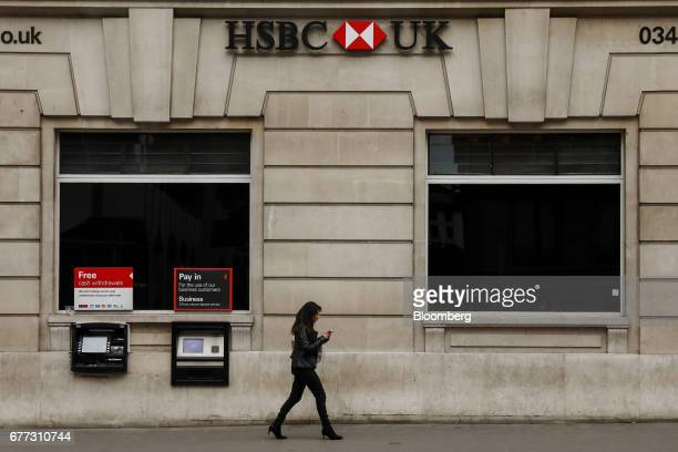 A pedestrian passes a HSBC Holdings Plc bank branch in London UK on Tuesday May 2 2017 HSBC has appeased investors with $35 billion of share buybacks...
