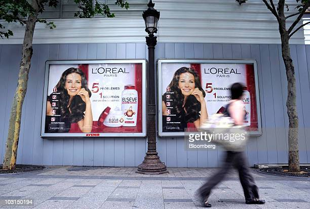 A pedestrian passes a JCDecaux SA Avenir advertising poster for L'Oreal SA products in Paris France on Wednesday July 28 2010 JCDecaux SA the world's...