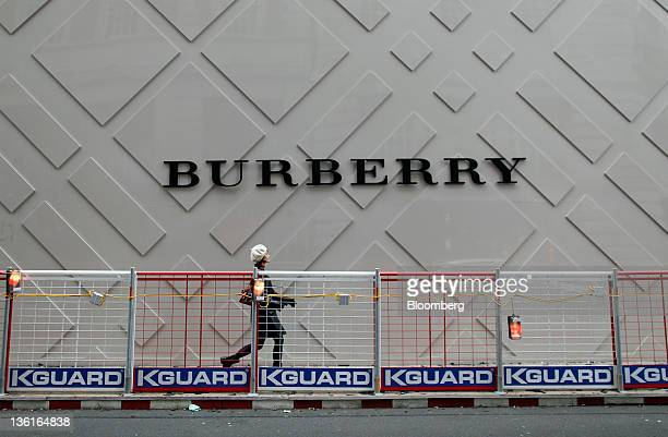 A pedestrian passes a logo for a new Burberry fashion store under construction on Regent Street in London UK on Tuesday Dec 27 2011 Britain faces the...