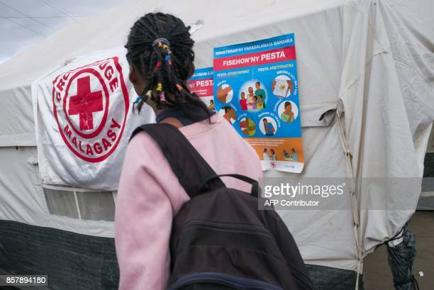 A pedestrian passes a Ministry of Health and Malagasy Red Cross healthcare checkpoint at the 'taxibrousse' station of Ampasapito district in...