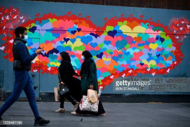 Pedestrian passes a mural thanking key workers for their efforts during the coronavirus pandemic in the centre of Leicester, central England, on June...