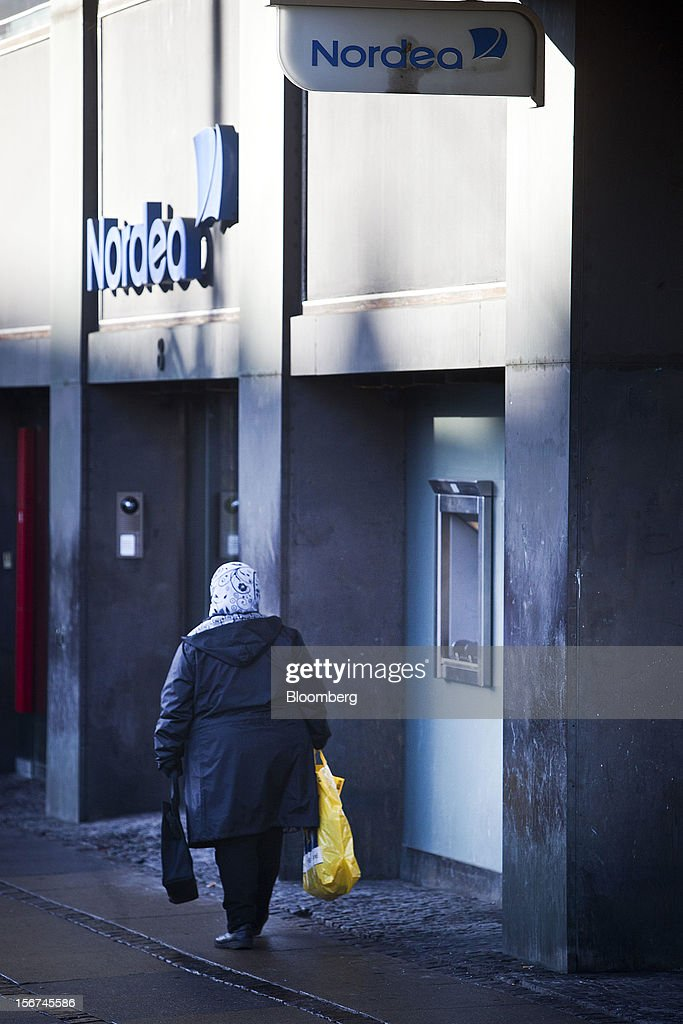 A pedestrian passes a Nordea Bank AB branch in central Copenhagen, Denmark, on Monday, Nov. 19, 2012. Denmark's two-year yields sank to the lowest in almost three months in Copenhagen trading as Europe's debt crisis continues to drive investors north. Photographer: Linus Hook/Bloomberg via Getty Images