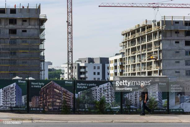 Pedestrian passes a residential apartment block construction site, on a plot of brownfield land in the Vysoany district in Prague, Czech Republic, on...