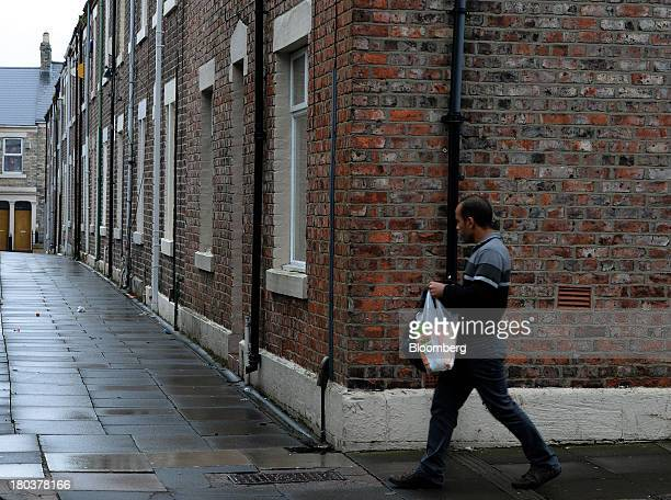 Pedestrian passes a row of terraced residential houses in Newcastle-upon-Tyne, U.K., on Wednesday, Sept. 11, 2013. U.K. House prices rose for a...