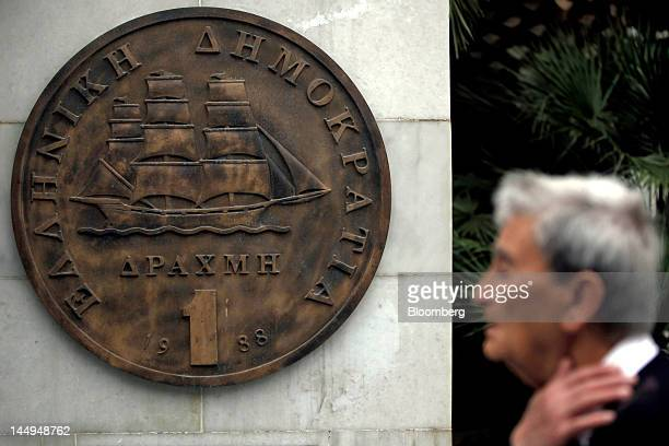 A pedestrian passes a sculpture of a one drachma coin in Athens Greece on Monday May 21 2012 Syriza's opposition to the terms of Greece's...