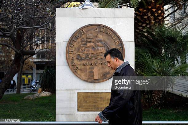 A pedestrian passes a sculpture of the Greek one drachma coin outside the Numismatic Museum of Athens in Athens Greece on Monday Dec 11 2011 If a...