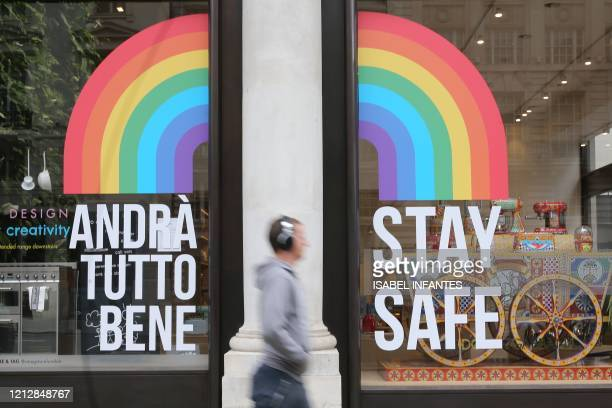 Pedestrian passes a shop window with a rainbow symbol of hope and the message to 'Stay Safe' in central London on May 13, 2020 as the coronavirus...