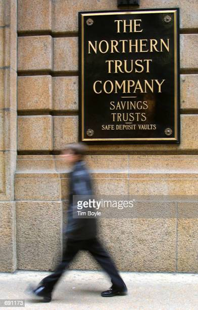 A pedestrian passes a sign mounted on an exterior wall of the Northern Trust Bank January 15 2002 in Chicagos downtown financial district Northern...