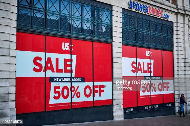 A pedestrian passes a sign offering up to 50 percent off goods in a Sports Direct International Plc retail store in Leeds UK on Thursday Dec 27 2018...