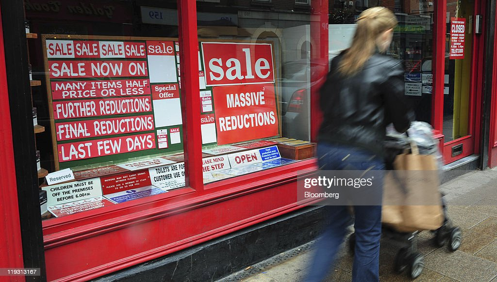 A Pedestrian Passes Signwriting Store With Window Display Of