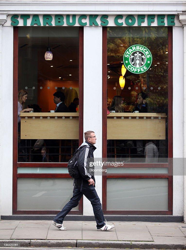 A Pedestrian Passes A Starbucks Corp Coffee Shop In London