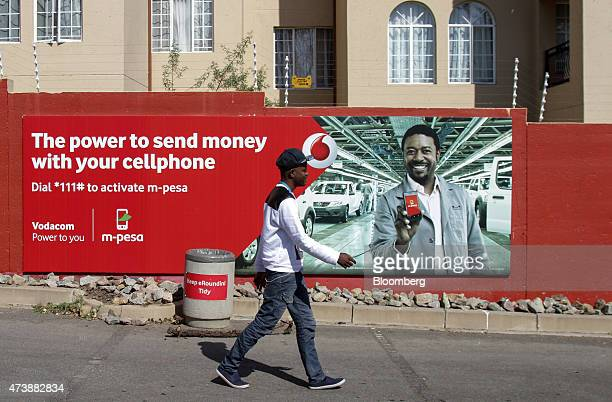 A pedestrian passes a street advertisement for Vodacom Group Ltd's Mpesa mobile payment services in Johannesburg South Africa on Monday May 18 2015...