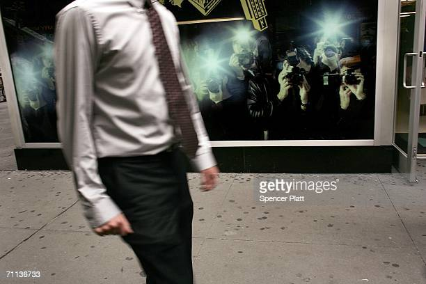 A pedestrian passes a wall with an image of photographers June 6 2006 in New York City According to the Bible's Book of Revelation 666 is the mark of...