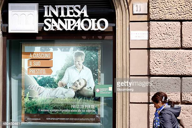 A pedestrian passes an advertisement for a personal loan displayed in the window of an Intesa Sanpaolo SpA bank branch in Rome Italy on Monday March...