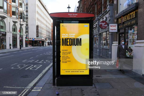 Pedestrian passes an advertisement in a Bus Stop, displaying the current Local Covid Alert Level is Medium in London, U.K., on Thursday, Oct. 15,...