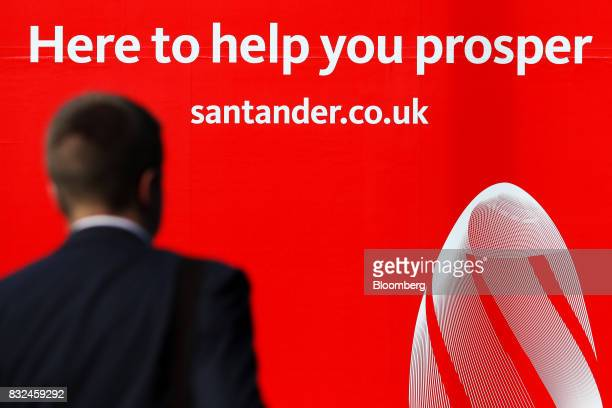 A pedestrian passes an advertising hoarding outside the offices of Banco Santander SA in London UK on Tuesday Aug 15 2017 Banco Santander Spains...