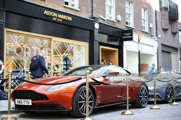 A pedestrian passes an Aston Martin DB11 automobile parked outside 'Aston Martin at No 8 Dover Street' luxury brand experience boutique by Aston...