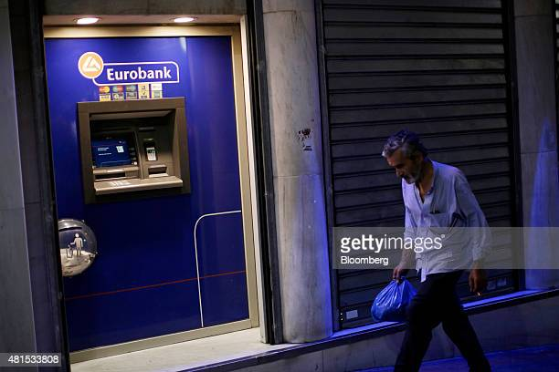A pedestrian passes an automated teller machine operated by Eurobank Ergasias SA at night in Athens Greece on Tuesday July 21 2015 Greek lawmakers...