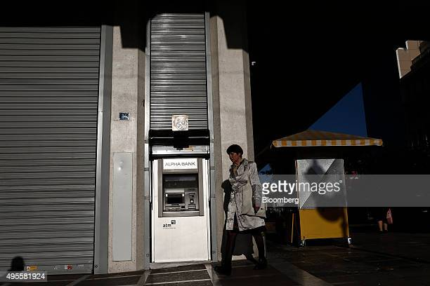 A pedestrian passes an automated teller machine partly covered by steel shutters outside an Alpha Bank AE bank branch in Athens Greece on Tuesday Nov...