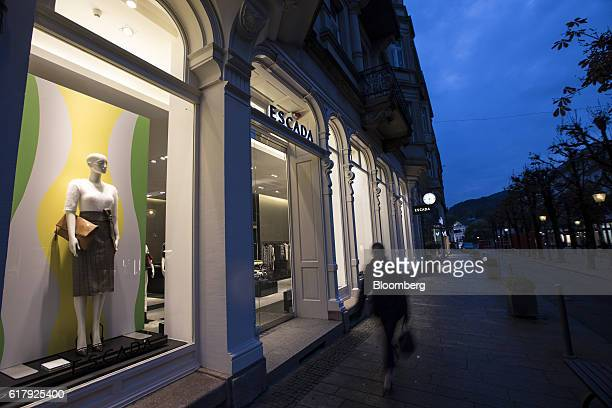 A pedestrian passes an Escada luxury clothing store at dusk in BadenBaden Germany on Monday Oct 24 2016 The world's luxurygoods market stopped...