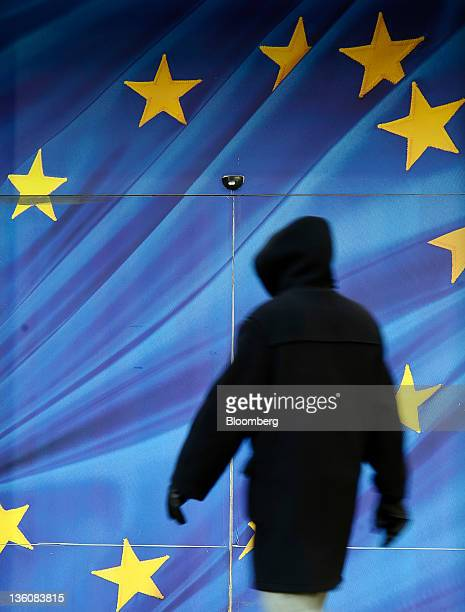 A pedestrian passes an image of the European Union flag outside the the European Commission headquarters in Brussels Belgium on Monday Dec 19 2011...