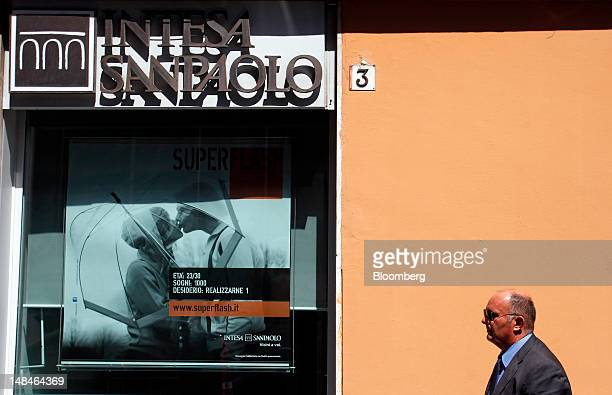 Pedestrian passes an Intesa Sanpaolo SpA bank branch in Rome, Italy, on Tuesday, July 17, 2012. UniCredit SpA and Intesa Sanpaolo SpA were among 13...