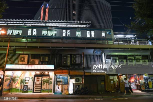 Pedestrian passes an Izakaya restaurant as an East Japan Railway Co.'s Keihin-tohoku line train stops at Yurakucho station in Tokyo, Japan, on...