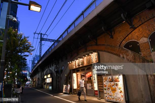 Pedestrian passes an Izakaya restaurant built under railway tracks in Tokyo, Japan, on Thursday, Sept. 3, 2020. In Tokyo, the spaces beneath elevated...