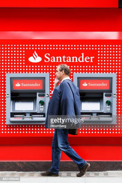 A pedestrian passes automated teller machines outside a bank branch of Banco Santander SA in London UK on Tuesday Aug 15 2017 Banco Santander Spains...