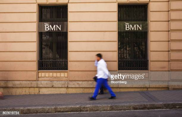 A pedestrian passes bank logos in the barred windows of a Banco Mare Nostrum SA bank branch in Madrid on Wednesday June 28 2017 Bankia SAagreed to...
