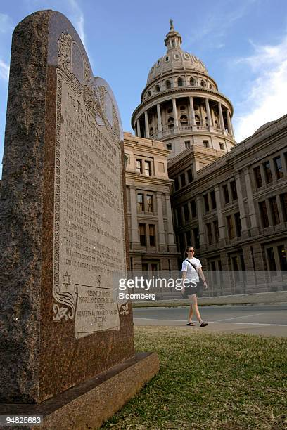 A pedestrian passes between a monument to the Ten Commandments and the Texas State Capital in Austin Texas Thursday February 17 2005 The monument was...
