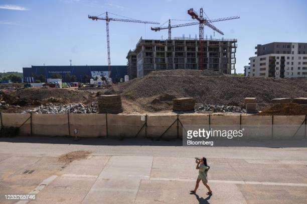 Pedestrian passes building materials on a residential apartment block construction site, on a plot of brownfield land in the Vysoany district in...