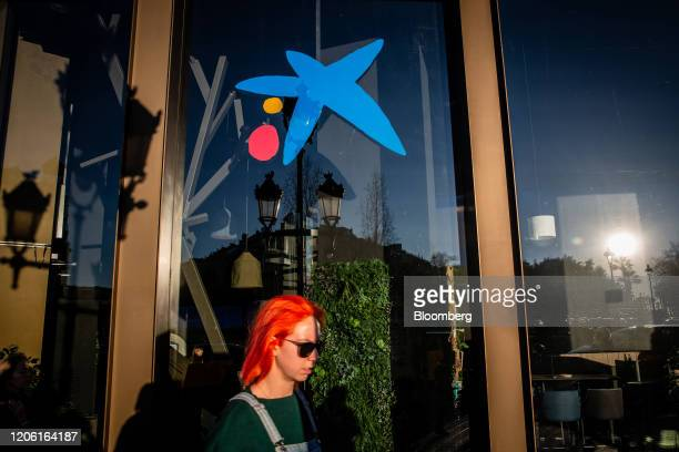 A pedestrian passes by a CaixaBank SA bank branch in Barcelona Spain on Thursday March 5 2020 Spanish bank shares soared after the European Unions...