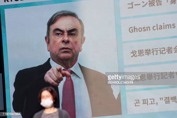 TOPSHOT A pedestrian passes by a huge screen showing a news program featuring former Nissan chief Carlos Ghosn in Tokyo on January 9 2020 Japan's...