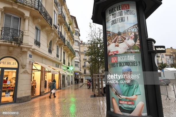A pedestrian passes by an advertising pillar with a poster launched at the request of Beziers' mayor as part of a campaign in favor of the TGV in the...