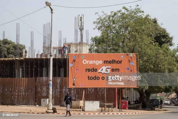 A pedestrian passes by an Orange Bissau SA '4G' billboard in Bissau GuineaBissau on Saturday Feb 10 2018 The International Monetary Fund said an...