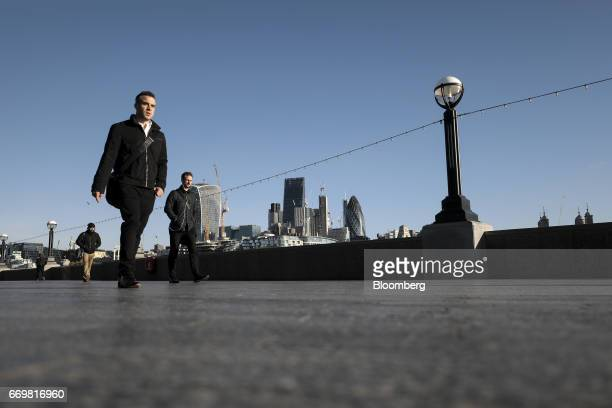 A pedestrian passes by as skyscrapers including Tower 42 the Heron Tower the Leadenhall building also known as the 'Cheesegrater' 30 St Mary Axe also...