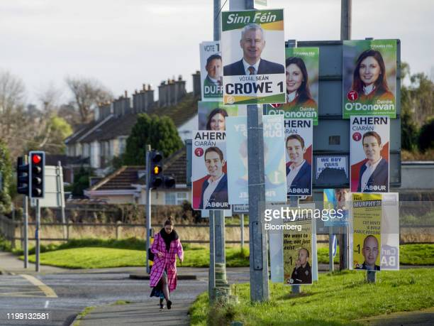 A pedestrian passes by general election posters for various political parties in Dublin Ireland on Thursday Feb 6 2020 Ireland votes in ageneral...