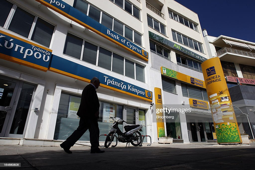 A pedestrian passes closed branches of Piraeus Bank SA, right, and Bank of Cyprus Plc, left, in Athens, Greece, on Tuesday, March 26, 2013. Piraeus Bank SA acquires Greek units of Cypriot lenders for total cash consideration of EU524m, according to e-mailed statement from the Athens-based lender today. Photographer: Kostas Tsironis/Bloomberg via Getty Images