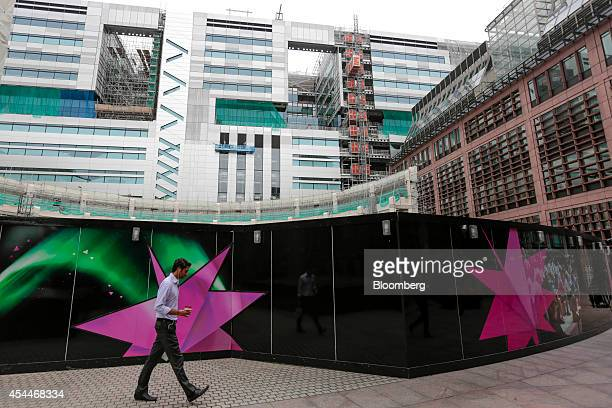 A pedestrian passes construction hoardings in Broadgate Circus as building work continues at the site of UBS AG's new office complex at No 5...