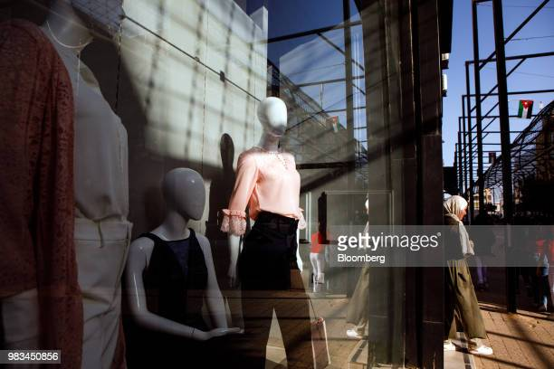 A pedestrian passes fashion mannequins in the window of a clothing store in the Sweifieh district of Amman Jordan on Thursday June 21 2018 President...