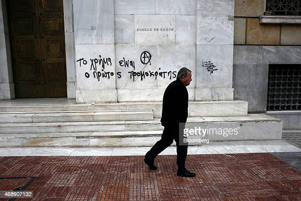 A pedestrian passes graffiti reading Money is the first terrorist on a wall outside the headquarters of the Bank of Greece SA in Athens Greece on...